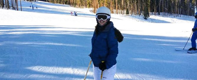 Woman standing in her ski gear on a ski slope.