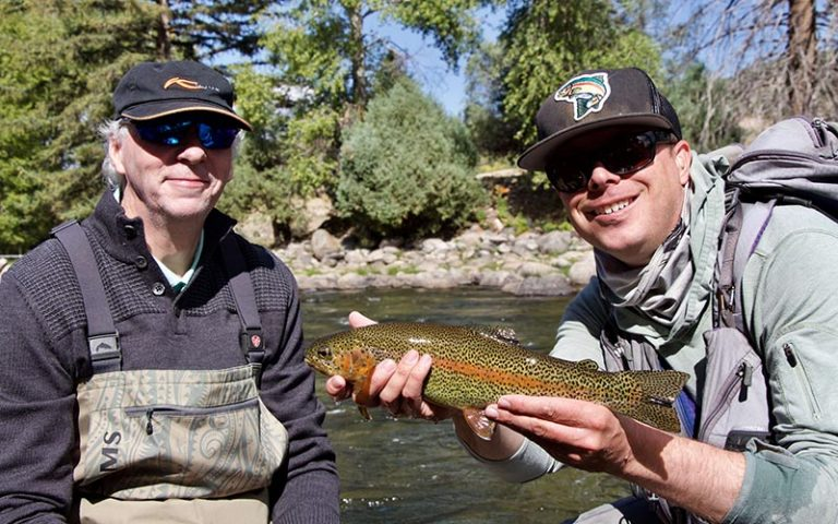 Two men sit in front of a river holding a fish they caught in one of the best Places to Fish in Colorado